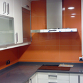 Cocina alicatada con azulejo naranja.