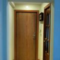 Entrada a vivienda con vista de la puerta de entrada recuperada y de la cocina.