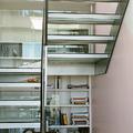 Escalera Suspendida en vidrio y librería en hueco de escalera