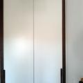 Frente de armario de puertas correderas lisas de suelo a techo lacadas en blanco con tapetas y tiradores en nogal americano con veta en vertical