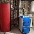 Instalación de caldera ATMOS DC25S de gasificación de leña con puerta para quemador de pellet