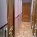 Instalación de zócalo de papel pintado en pasillo.