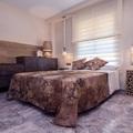 Dormitorio con cortinajes y ventana como cabecero