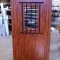 Puerta color madera con reja metálica
