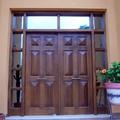 Puerta de entrada en pino melis macizo tintado en color nogal.