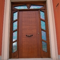 Puerta de entrada principal en pino tea tintado en color nogal claro.