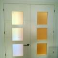Puerta lacada en blanco de dos hojas con entrecalles horizontales, vidrio mateado y manilla en L