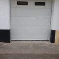 Puerta seccional acananalada blanca con ventanas.