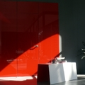 Revestimiento de pared en vidrio rojo brillo y puerta enrasada mismo acabado