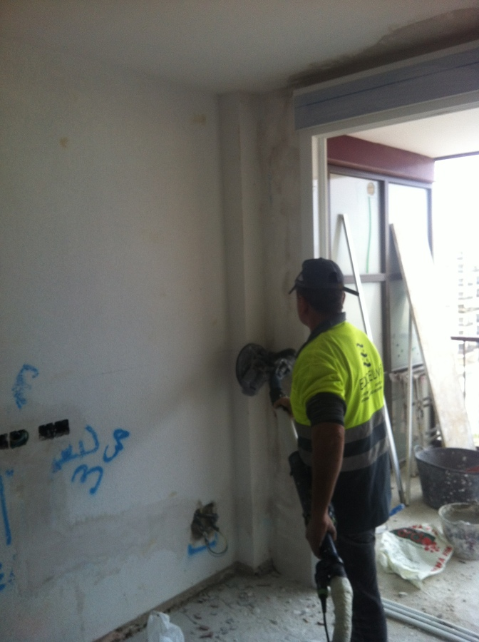 Alisando paredes para pintar en liso.