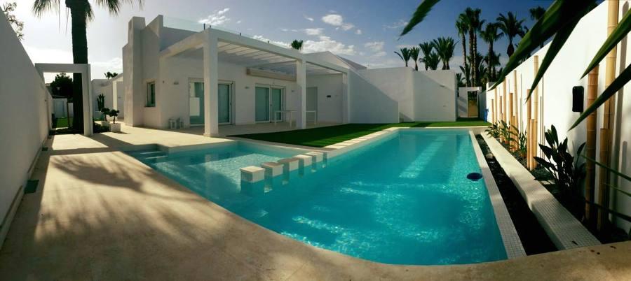 """piscina tipo """"Infinity"""" con revestimiento vítreo blanco y piedra caliza, en puerto rey (Vera)."""