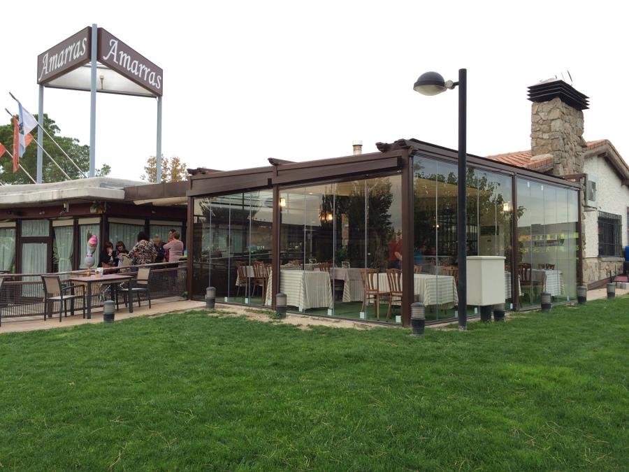 Cerramiento de terraza mediante pérgola de lona doble y cortinas de cristal