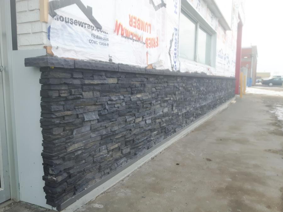 Colocación piedra rústica sobre fachada de negocio.