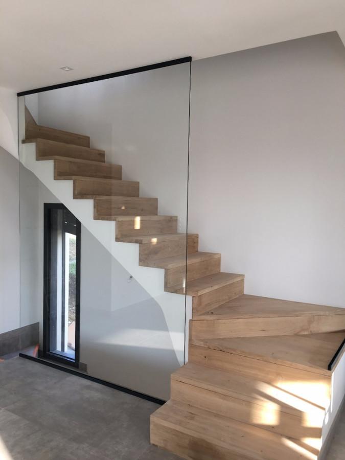 Escalera en madera de riga y baranda en vidrio