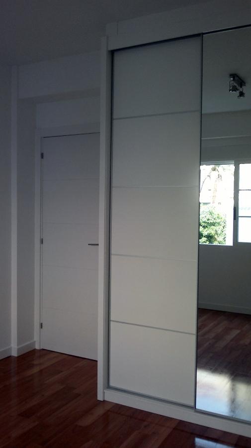 armario a medida.techos y paredes de pladur,puerta de paso blanca con rayas.tarima flotante quick step