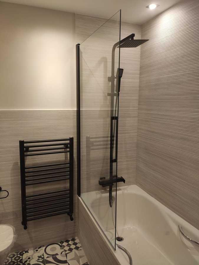 Detalle en Baño, mampara, ducha y toallero negro