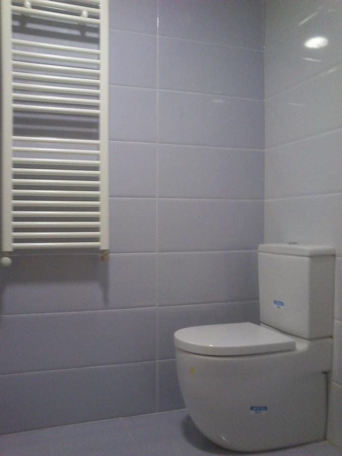 Azulejo normal, radiador-toallero y sanitario pegado a la pared.