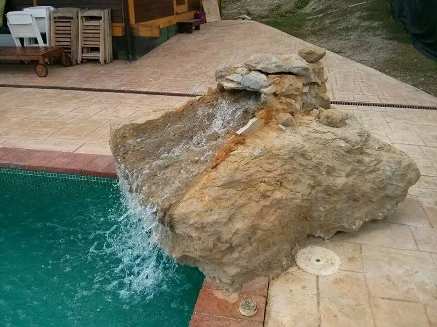Foto cascada sobre roca en piscina privada de fuentes for Ideas de piscinas con cascadas