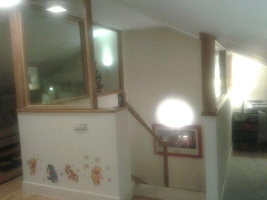cerramiento de buhardilla haciendo juego con la escalera de cristal y madera
