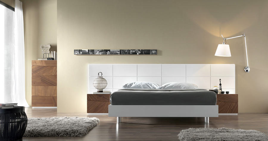 Dormitorio con cabecero panelado en laca blanca.