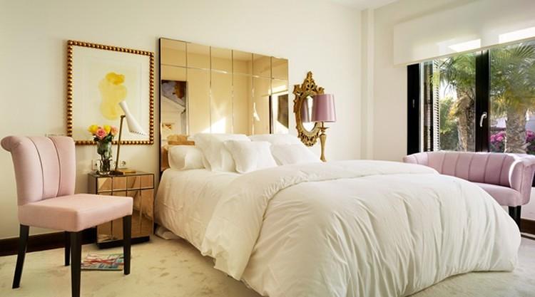 Dormitorio de estilo retro con cabecero de espejo.