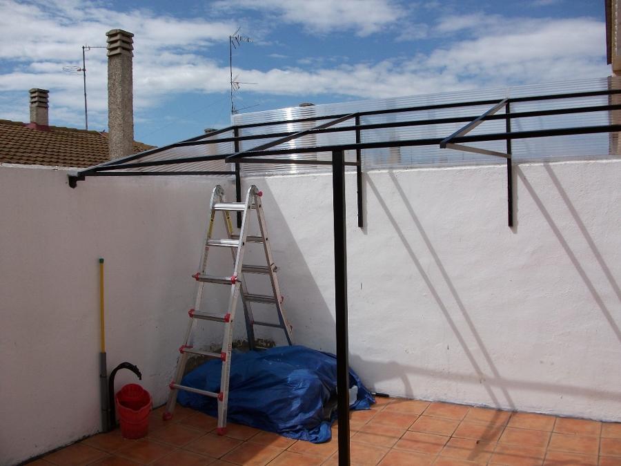 hacemos todo tipos de trabajos de carpintería metálica, aquí instalamos un tejado con estructura de hierro y placa de p.v.c imitación  de tejas ,y metacrilato  .