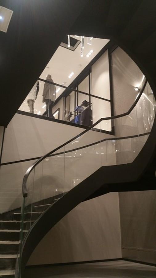 Detalle de escalera metálica helicoidal con barandilla de cristal curvo