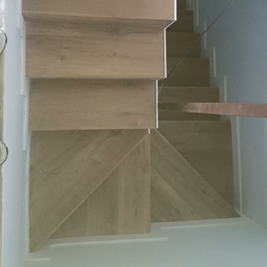 Escalera forrada de tarima quick step y rodapié blanco