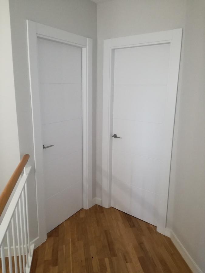 Puertas lacadas en blanco, suelo flotante de roble
