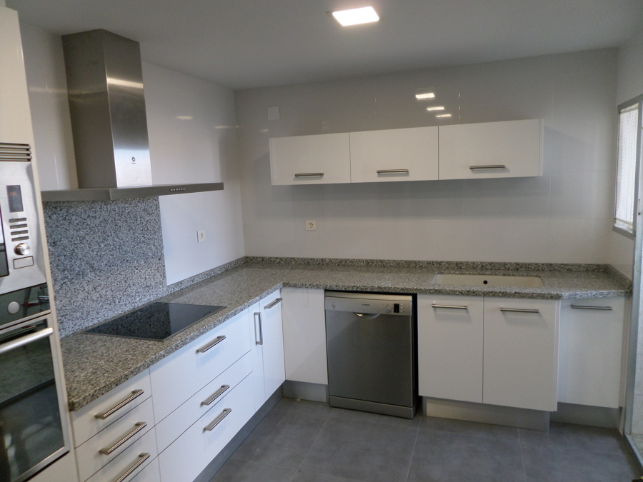 Bancada de cocina en granito gris perla con aplacado en la zona de la