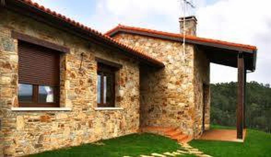 Foto casa con fachada de piedra de construcciones for Puertas prefabricadas precios