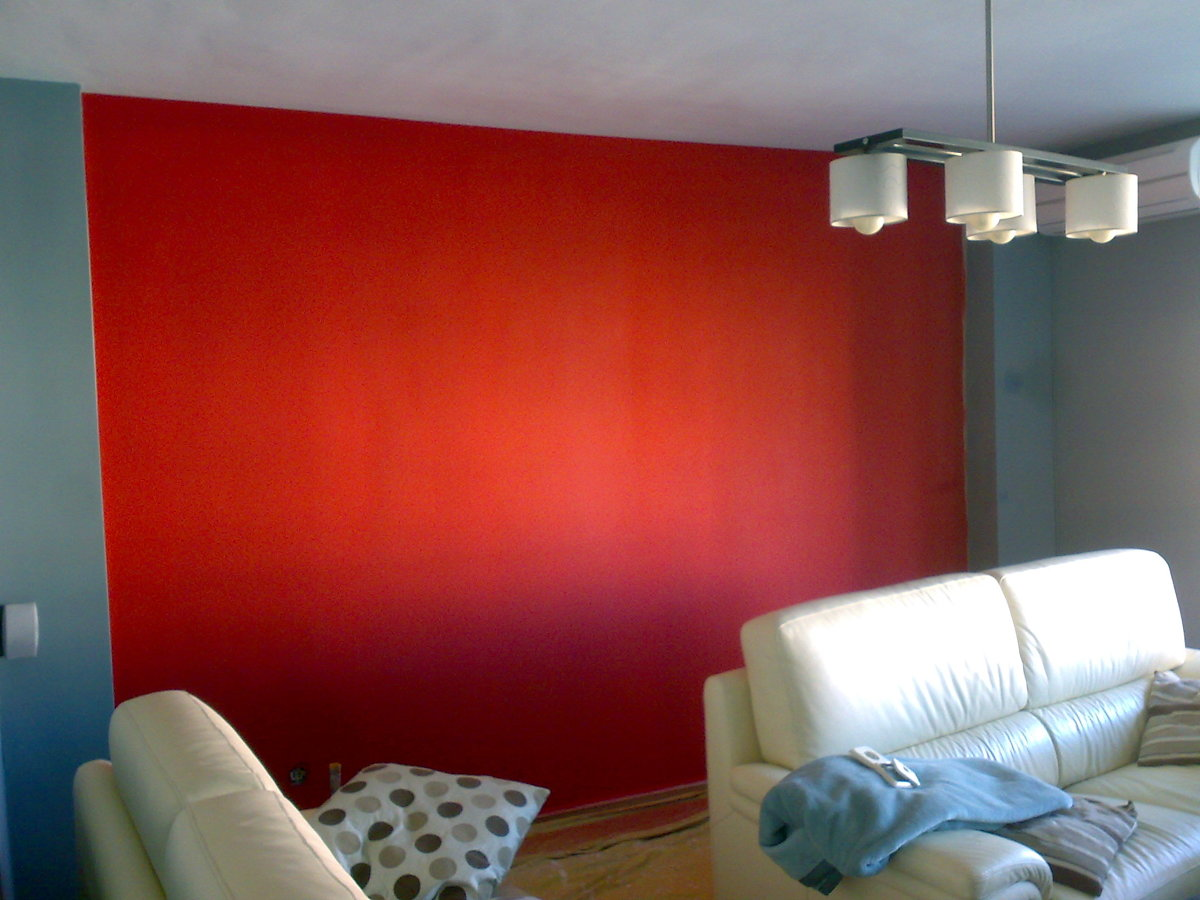 Pared pintada de rojo en salon de vivienda contrastada con gris