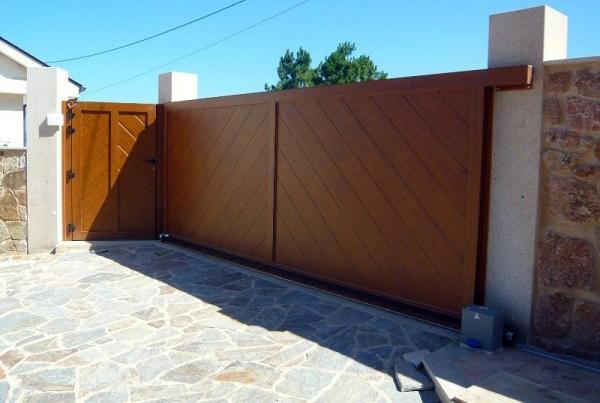 Foto puerta corredera imitaci n madera de tecnipuertas for Puerta corredera exterior jardin