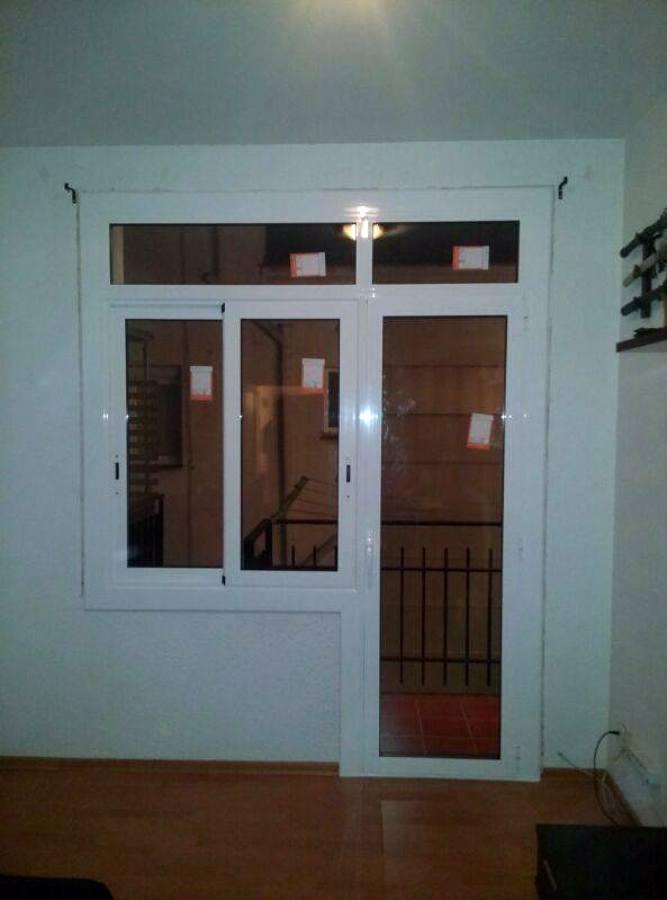 Puerta practicable de una hoja con ventana corredera