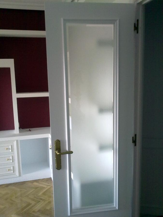 Puerta restaurada con esmalte en blanco y vidrio mateado con bisel