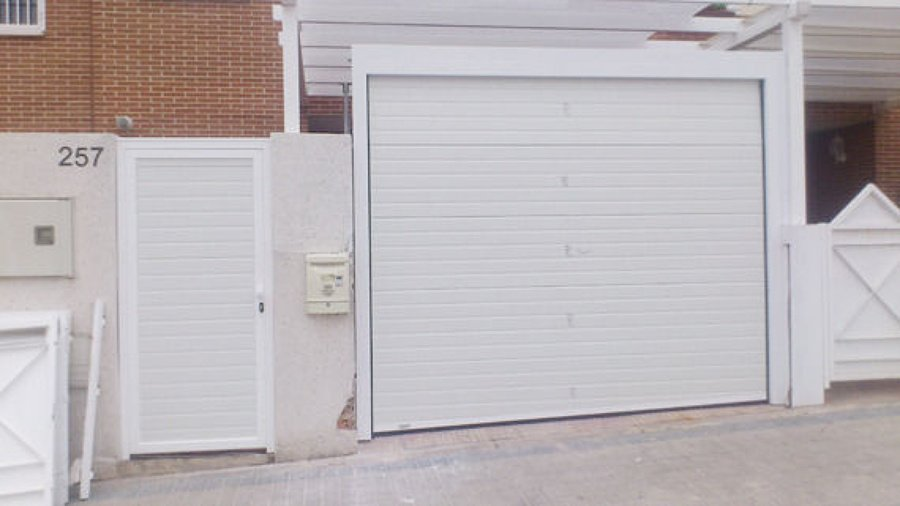 Foto puerta seccional acanalada blanca con peatonal al for Puertas de garaje precios