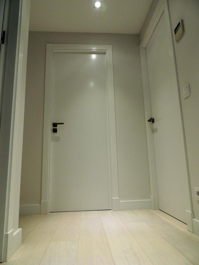 Puertas lisas lacadas con plintos, tarima natural con rodapié lacado.