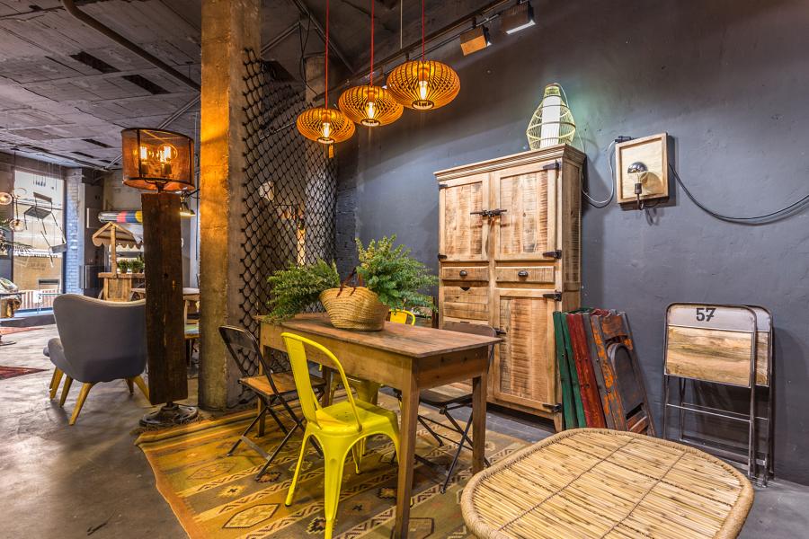 Mesa de taller, sillas metálicas y de madera, alacena de madera tropical, lámparas con bombillas de filamentos.