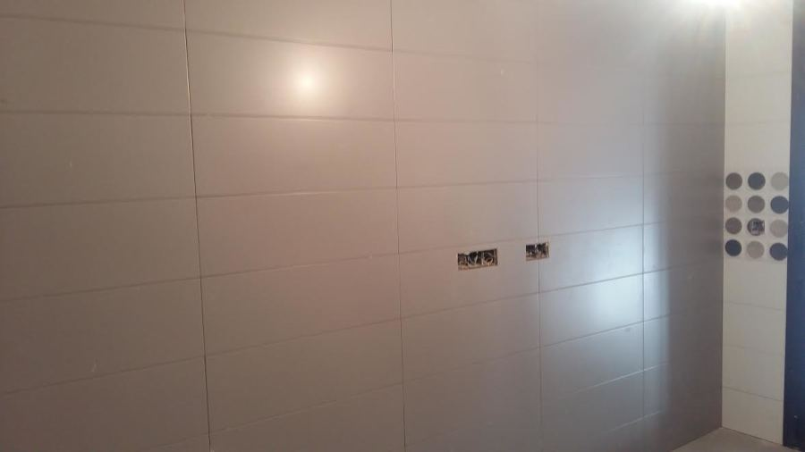 Proceso de alicatado de paredes en cuarto de caldera.