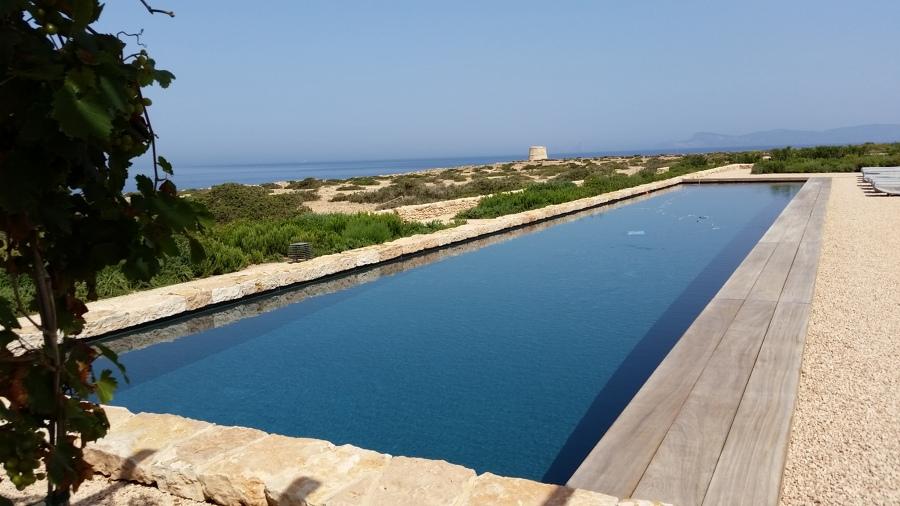 Piscina exterior en Baleares, de 24m x 4.50m desbordante oculto bajo tarima