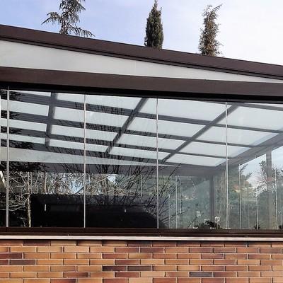 Instalación de techo móvil con estructura completa de soporte y vidrio traslúcido y cortinas de cristal como cierre vertical.