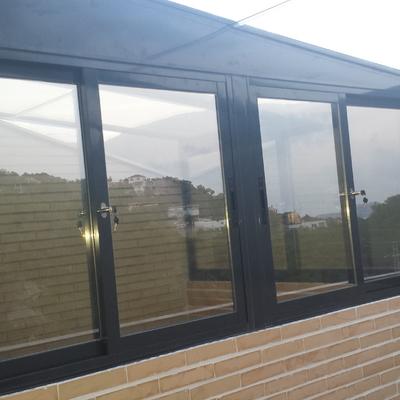 Cerramiento total terraza ladrillo visto ventanas y techo aluminio y cristal.