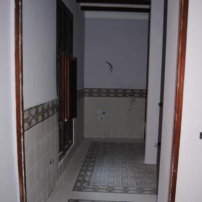Azulejo de ceramica en baño con alfombra en suelo y cenefa en pared