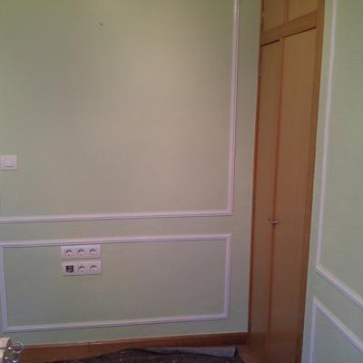 Sala de estar en color verde con moldura en blanco