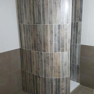 Muro curvado en ducha con azulejo imitación madera.
