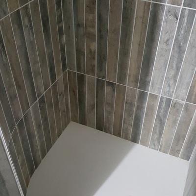 Interior de ducha con muro en curva.