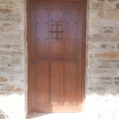 Pared de piedra natural y puerta de madera