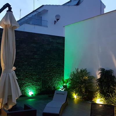 Patio con muro llorón iluminado con mobiliario de jardín