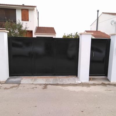 Puerta corredera y puerta peatonal pintadas en negro extremadamente brillante