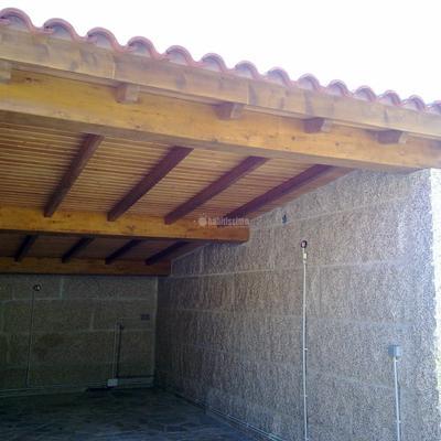 Construcción de garaje y barbacoa con estructura de madera y panel sandwich de madera.